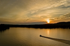 Sun setting over boat on 1st Lake from drone on South Shore Acres Road 2, Old Forge, NY